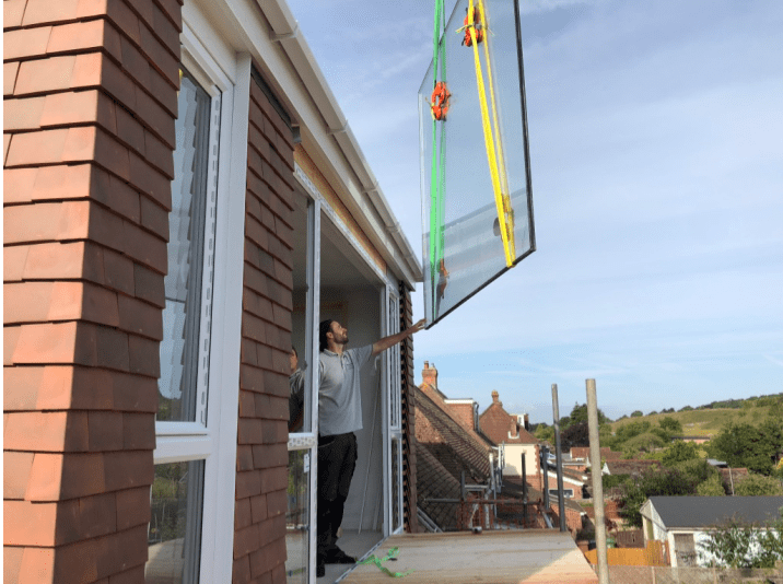 The insertion of laminated safety glass by means of crane to a loft conversion.