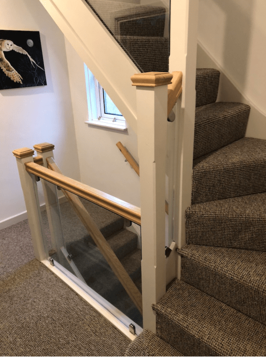 Staircase has oak handrail with 10mm toughened glass panels. Stainless steel brackets.